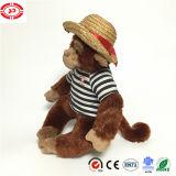 Jouet mou bourré mignon de port se reposant de chapeau de T-shirt de singe de peluche
