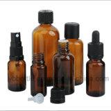 Botellas de cristal, redondos ambarinos con los cuentagotas negros del vidrio del bulbo