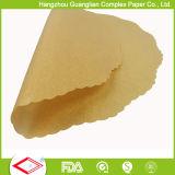 El papel de pergamino antiadherente sin blanquear circunda trazadores de líneas redondos del molde para pasteles