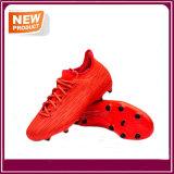 人のためのオレンジフットボールのサッカーの靴
