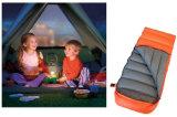 子供は屋外のキャンプの寝袋のアヒルを模倣する