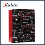 光沢のある薄板にされたアートペーパーのクリスマスの赤く及び黒いギフトの紙袋