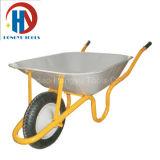 O edifício utiliza ferramentas o carrinho de mão de roda para o trabalhador do concreto da construção