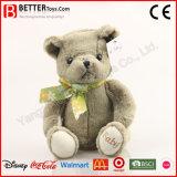 Urso do brinquedo do animal enchido em um laço de curva para o bebê