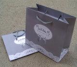 La qualité conçoivent le sac de papier estampé de cadeau avec le traitement de bande