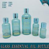 Покрасьте вокруг штемпелевать изготовленный на заказ малой стеклянной бутылки эфирного масла горячий