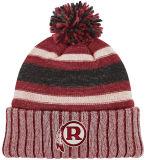 手は帽子のポンポンの手によって編まれた帽子のポンポンを編んだ