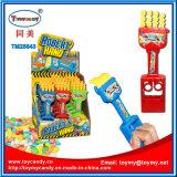 プラスチックロボット手はキャンデーが付いているおもちゃをからかう