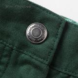 Capretti verdi che coprono i pantaloni dei pantaloni delle ragazze dell'indumento dei bambini