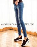 A fêmea da alta qualidade veste calças magros do lápis das calças de brim do furo