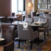 Tabelas e cadeiras lustrosas elevadas pretas do restaurante para jantar