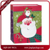 品質表示票およびサテンのリボンのハンドルが付いているクリスマスのサンタクロースのショッピングギフトの紙袋