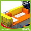 Sosta del trampolino di ginnastica di sport dell'interno con la stuoia di salto olimpica