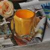 カラーによって吹きかけられる奉納のガラス蝋燭のコップ