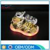 O diodo emissor de luz dourado bonito da forma da cor calç sandálias claras para mulheres