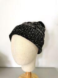 女性の方法Pomponが付いている冬によって編まれるシュニールの帽子