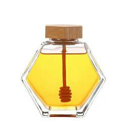 木のふたが付いている工場によって作り出される卸し売り空の六角形のガラス蜂蜜の瓶かディッパーまたはステッカー