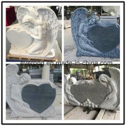 中心によって切り分けられる墓石との安い灰色か黒い花こう岩の天使