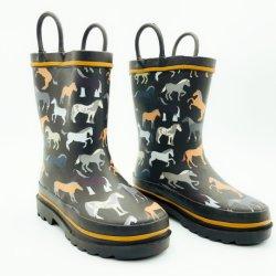 男の子の暗い灰色の馬は屋外の雨靴の防水ゴム長をからかう