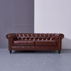 居間の余暇のチェスターフィールド型のソファの革ソファー