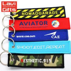 I regali promozionali comerciano il prodotto all'ingrosso intessuto ricordo unico su ordinazione poco costoso Keychains di marchio del ricamo di corsa di marca dell'anello portachiavi di marchio