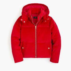 優雅な冬の冷たい防護衣の女性は赤いコーデュロイのパッファーのジャケットのコートを調整する