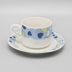 O copo de cerâmica azul e branco e Pires com adesivo