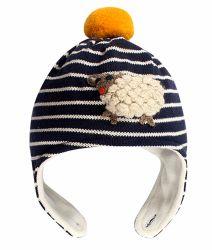 綿は帽子の暖かい動物によって模造された縞で飾られた冬の子供の帽子を編んだ
