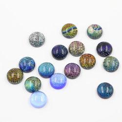 Silberne Schmucksachen zerteilen die dichroiken GlasCabochons, die für die hängenden Ohrringe befestigt werden