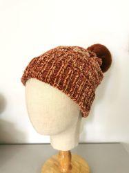 Pomponが付いている女性の方法冬のシュニールによって編まれる帽子