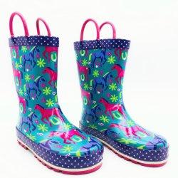 女の子の多色刷りの馬は屋外の雨靴の防水ゴム長をからかう
