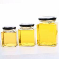 金属のふたが付いている正方形の形のガラスビンの蜂蜜のびん