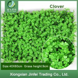 Belas plantas artificiais de plástico na parede verde exterior de flores artificiais