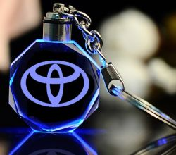 Preiswerte Laser3d octagon-Glasgroßhandelsfertigkeit KristallKeychain förderndes personifiziertes kundenspezifische Taschenlampen-Unternehmensandenken-Geschenk des Auto-Firmenzeichen-LED für Förderung