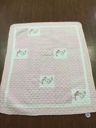Cama de bebê em estilo de patchwork com padrão de flor rosa