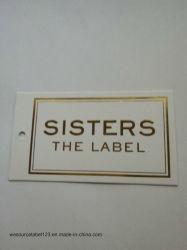 金ホイルデザイン品質表示票が付いている白く厚いカード