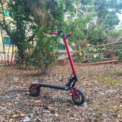 蹴りの電気スクーターの電気バイクを折っている新製品の大人
