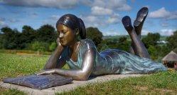 現代屋外の庭の装飾的なブロンズ彫刻の女の子の読本