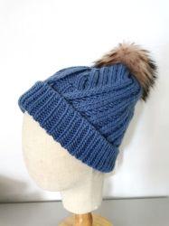 毛皮のPomponが付いている女性の冬の方法空想のパターンによって編まれる帽子
