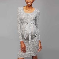 La maternità grigia elegante della parte anteriore del telaio copre il vestito incinto dalle donne
