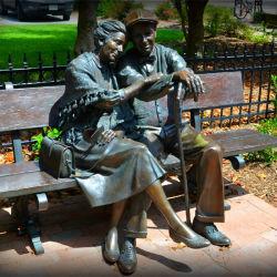 ベンチの彫像に坐る実物大の青銅色の愛情のある古いカップル