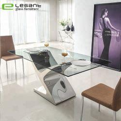 Grande tavolo da pranzo in acciaio inox con piano in vetro trasparente