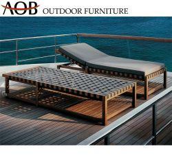 Удобная кровать возле бассейна шезлонги, раскинут плетеной мебели