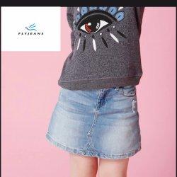 方法古典的なまっすぐな女の子ははえのジーンズによってデニムのスカートをショートさせる