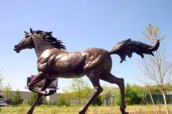 屋外の庭の大きく旧式な青銅色の馬の彫像