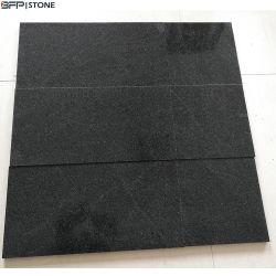 磨かれた暗い灰色の黒はまたは自然な花こう岩の石の床タイルを炎にあてるか、または砥石で研いだ