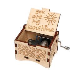ハンドメイドの旧式な木のおもちゃのオルゴールのクランクを手で回されたオルゴール