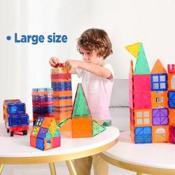 2 台の車が付いている子供は磁気の建物のブロックを置く