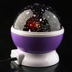 赤ん坊はLED回転夜ランプの星プロジェクター新型のおもちゃをもてあそぶ