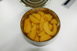 Pêche en conserve de fruits frais tranchés dans un sirop léger